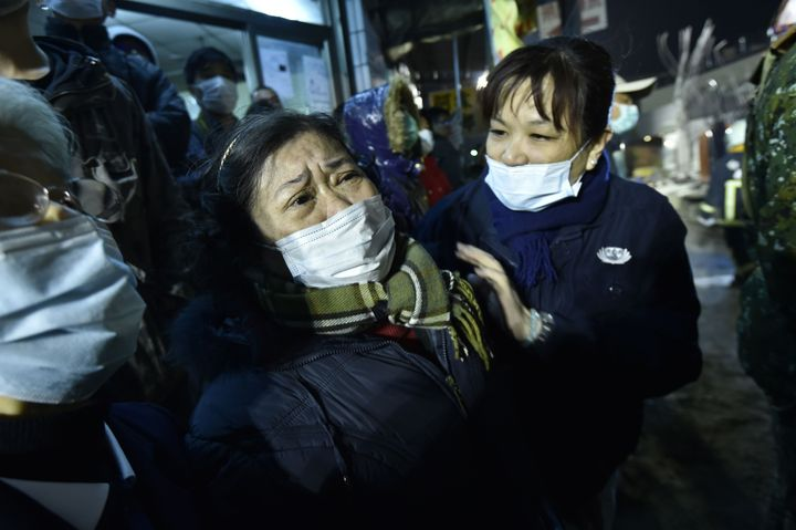A woman (C) is comforted as rescue personnel continue work at the site of a collapsed building in the southern Taiwanese city