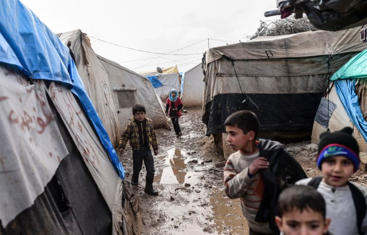 Refugee children walk between tents at a camp near the Turkish border crossing gate as Syrians fleeing the northern embattled