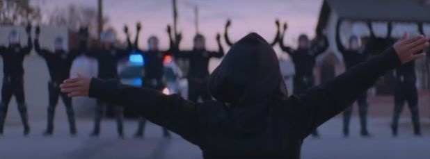 In another scene from the video, a young black boy in a black hoodie holds his arms out wide before a line of officers with t