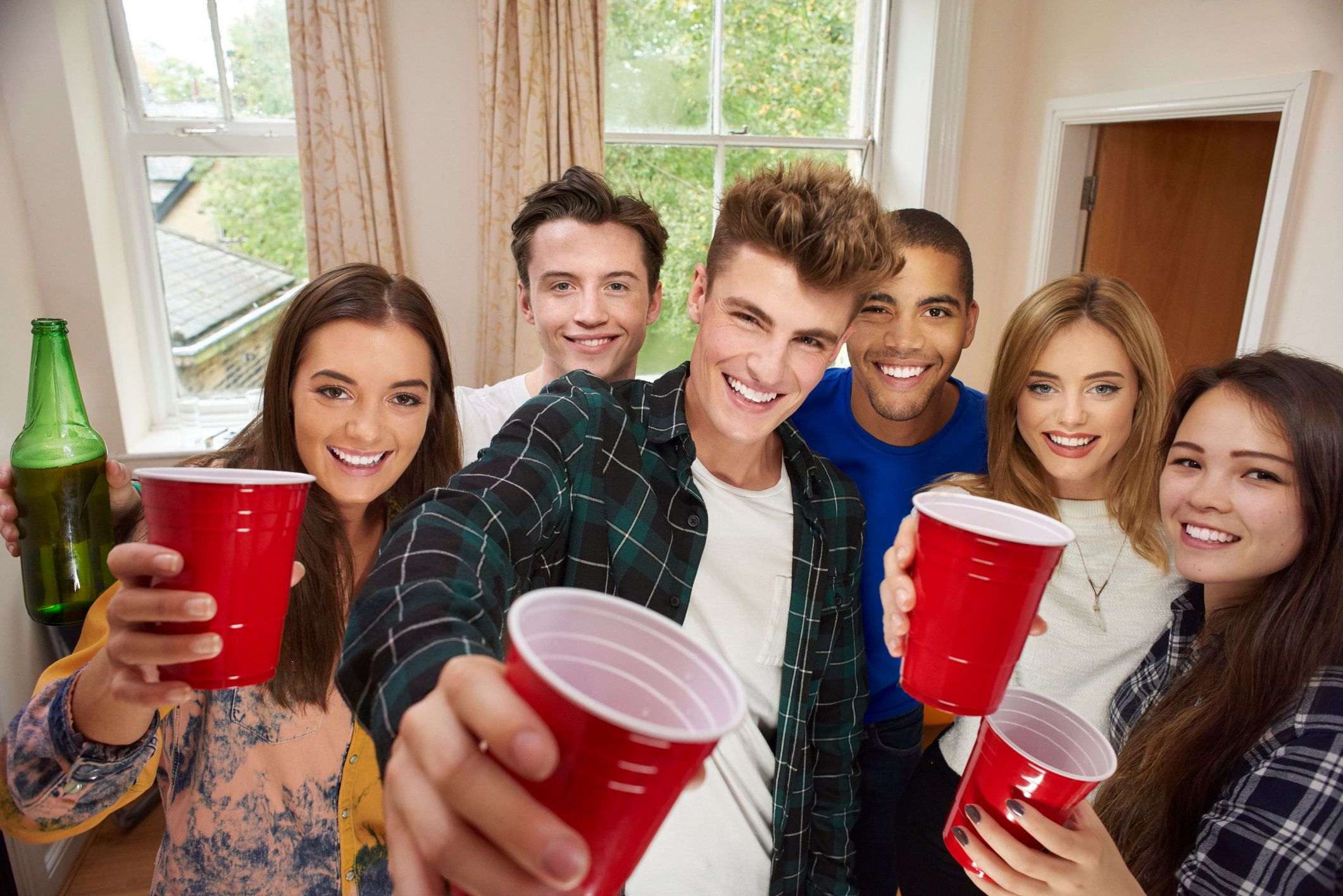 a mixed group of students sharing a house, have a pre-drinks party in their flat. They are drinking and dancing and messing about group hugging and looking at camera with a big cheers.