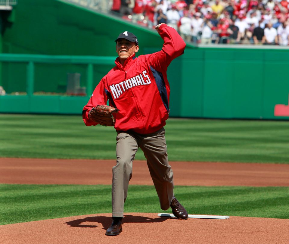 Wearing a Washington Nationals jacket and a Chicago White Sox hat, President Barack Obama delivers the first pitch of the Was