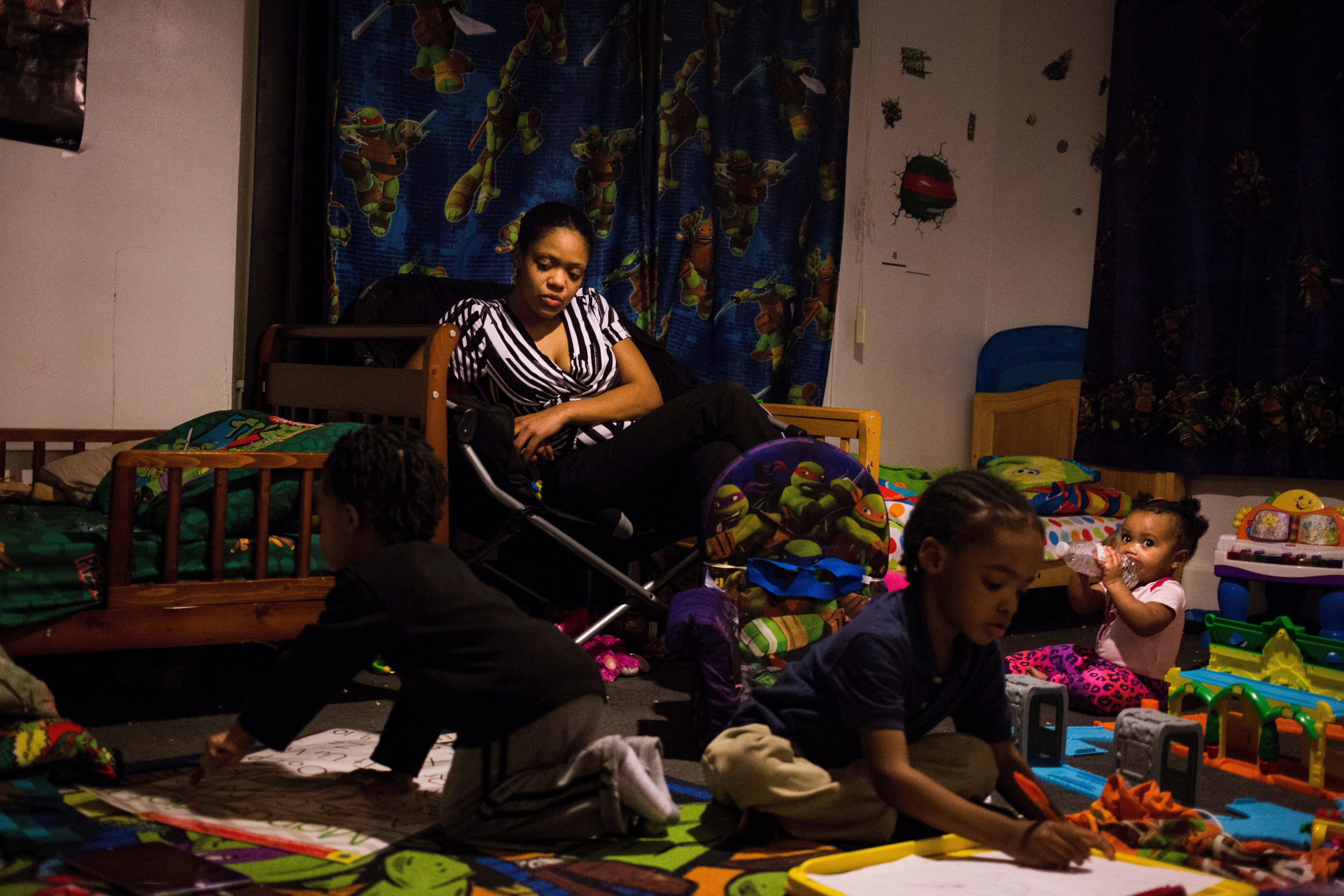 Brittny Giles, of Flint, Michigan, watches her sons practice drawing their letters at their home on Feb. 4, 2016.She no