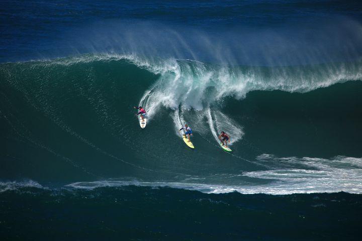 Surfers ride a wave during the 2009 Eddie Aikau Big Wave Invitational at Waimea Bay.
