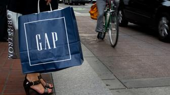 A pedestrian carriers a Gap Inc. shopping bag while waiting to cross Market Street in San Francisco, California, U.S., on Monday, July 7, 2014. U.S. same-store sales fell 1.2 percent month over month, according to the latest data released by Johnson Redbook Research. Photographer: David Paul Morris/Bloomberg via Getty Images