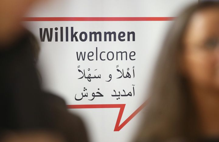 """Journalists stand near a sign with """"Welcome"""" written in German, English and Arabic at a new jobs counseling center for migran"""