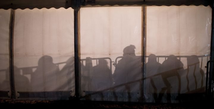 The shadows of asylum-seekers waiting for their registration are cast against the wall of a tent in front of the State Office