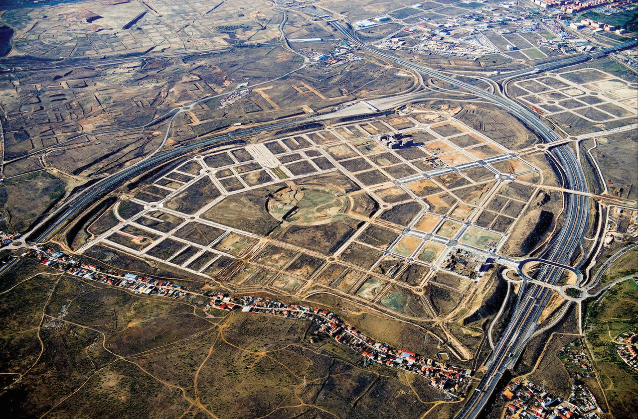 """The nearly-empty El Cañaveral development near Madrid, seen from above in 2014. The strip of housing in the foreground is La Cañada Real Galiana, said to be Europe's largest shantytown. Several years ago, Madrid <a href=""""http://www.npr.org/2012/04/27/150824559/showdown-looms-over-europes-largest-shantytown"""" target=""""_blank"""" role=""""link"""" class="""" js-entry-link cet-external-link"""" data-vars-item-name=""""demolished parts of the informal settlement"""" data-vars-item-type=""""text"""" data-vars-unit-name=""""56ba6221e4b0b40245c47dff"""" data-vars-unit-type=""""buzz_body"""" data-vars-target-content-id=""""http://www.npr.org/2012/04/27/150824559/showdown-looms-over-europes-largest-shantytown"""" data-vars-target-content-type=""""url"""" data-vars-type=""""web_external_link"""">demolished parts of the informal settlement</a>."""