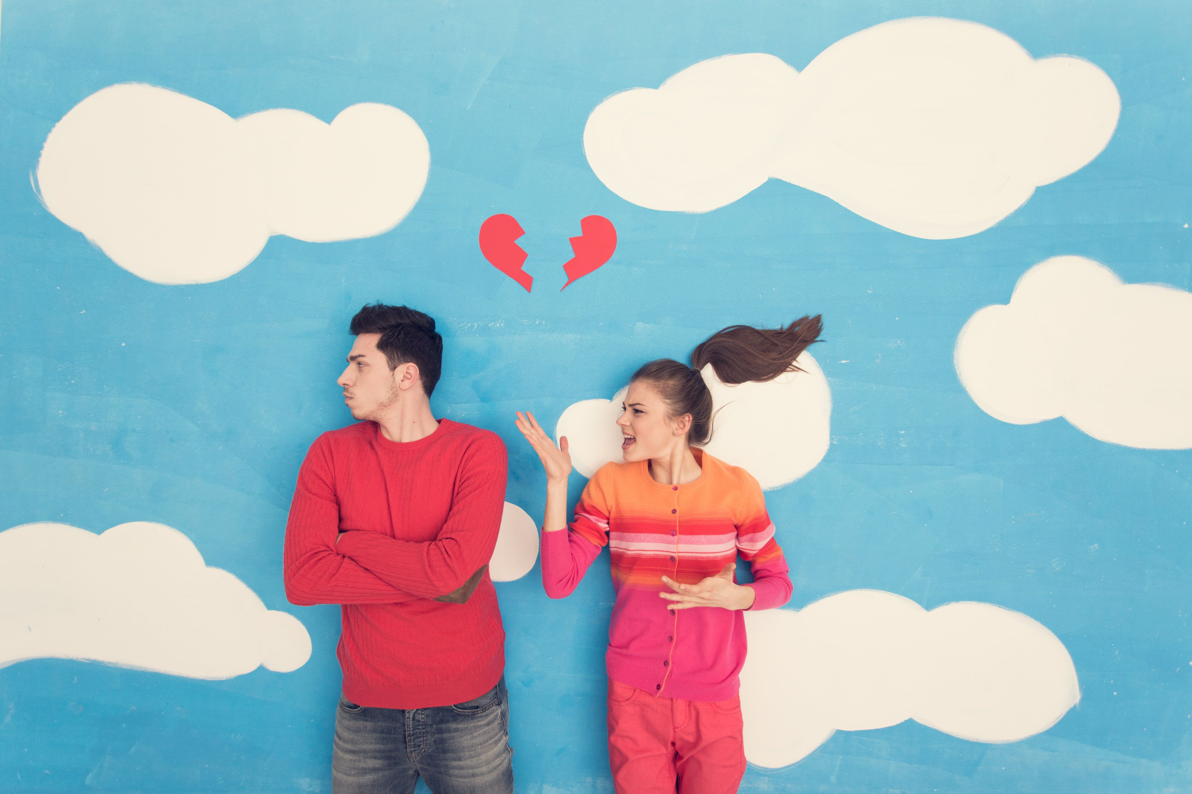 Young couple in a cartoon, directly above shot. Girl and boy on clouds and sky with broken red paper heart above their heads.