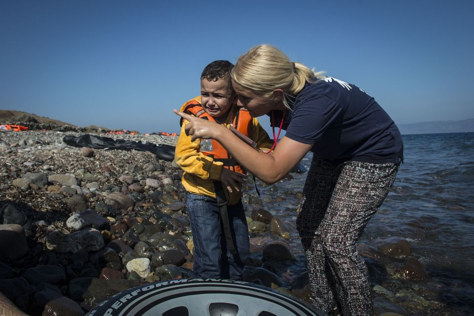 A European volunteer talks to a crying refugee toddler after refugee boat arrived in Lesbos Island, Greece...