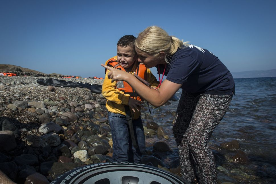 A European volunteer talks to a crying refugee toddler after refugee boat arrived in Lesbos Island, Greece on September 17, 2