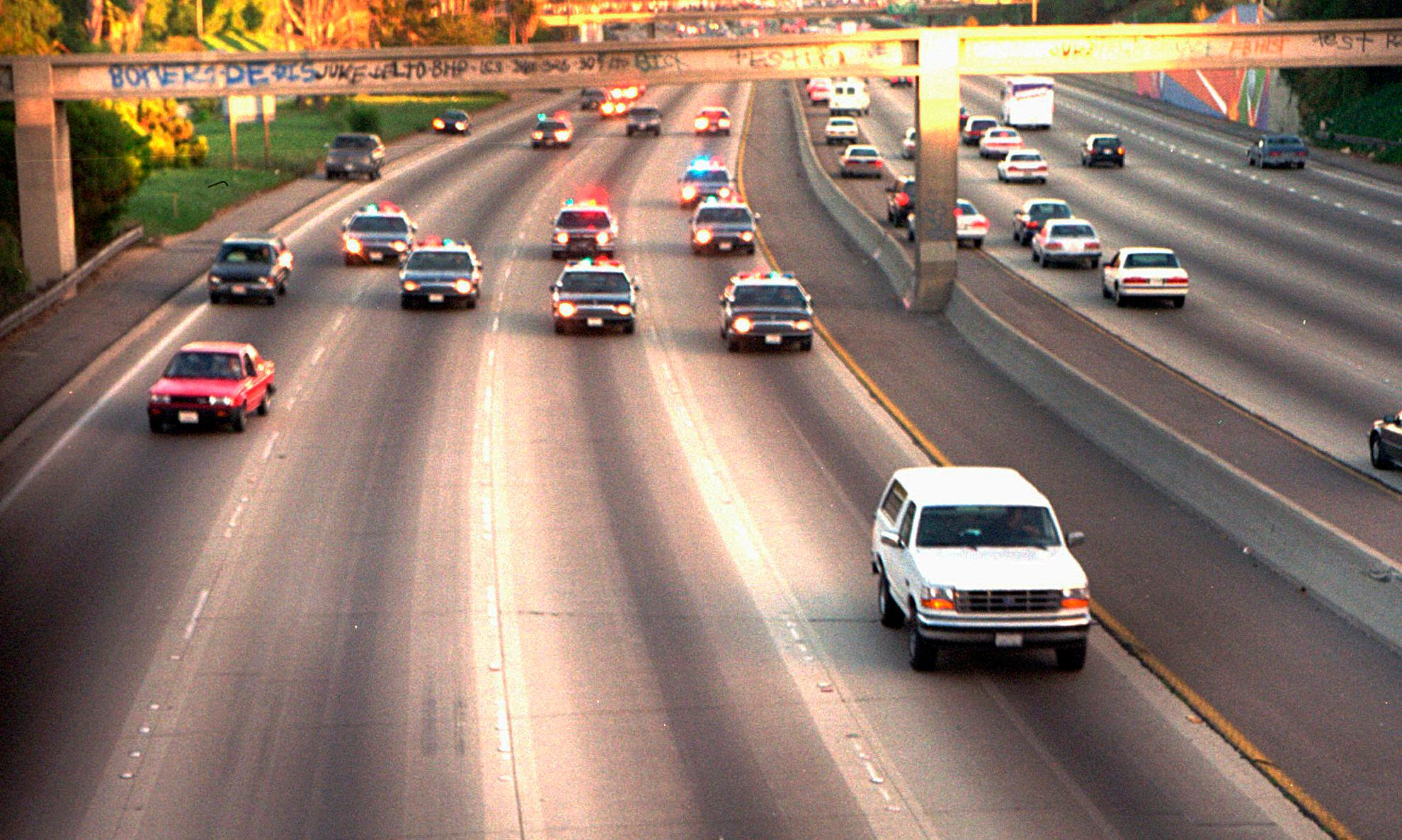 O.J. Simpson is trailed by LAPD cars as it travels along a California freeway.