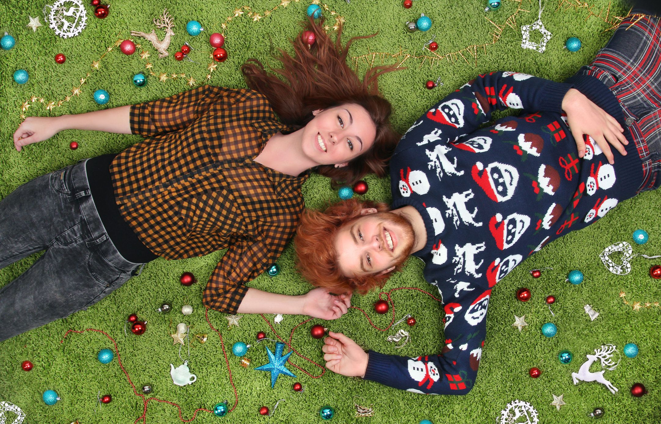happy couple with Christmas ornaments lying on the carpet