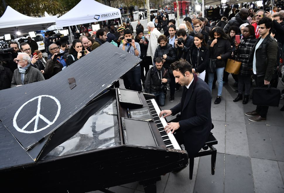 German Pianist Davide Martello, also known as Klavierkunst, plays piano as people gather after observing a minute of silence