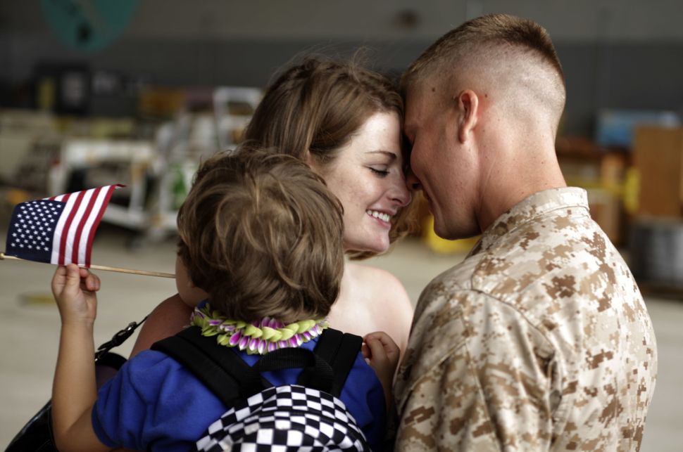 Savannah Dejong holding her son Rhone (3) greets her husband, Daniel with 1/3 Marines Bravo Company, upon his return to Hawai