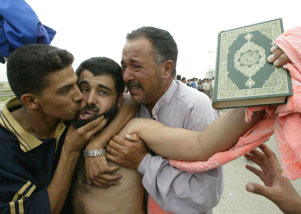 A freed prisoner holding up the Muslim holy Koran is hugged and kissed by family members after being released from the Abu Gh