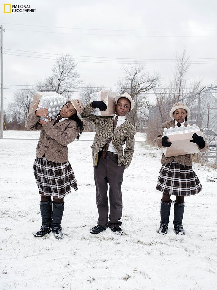 Siblings Julie, Antonio, and India Abram collect their daily allowance of bottled water from Fire Station #3. Located on Mart