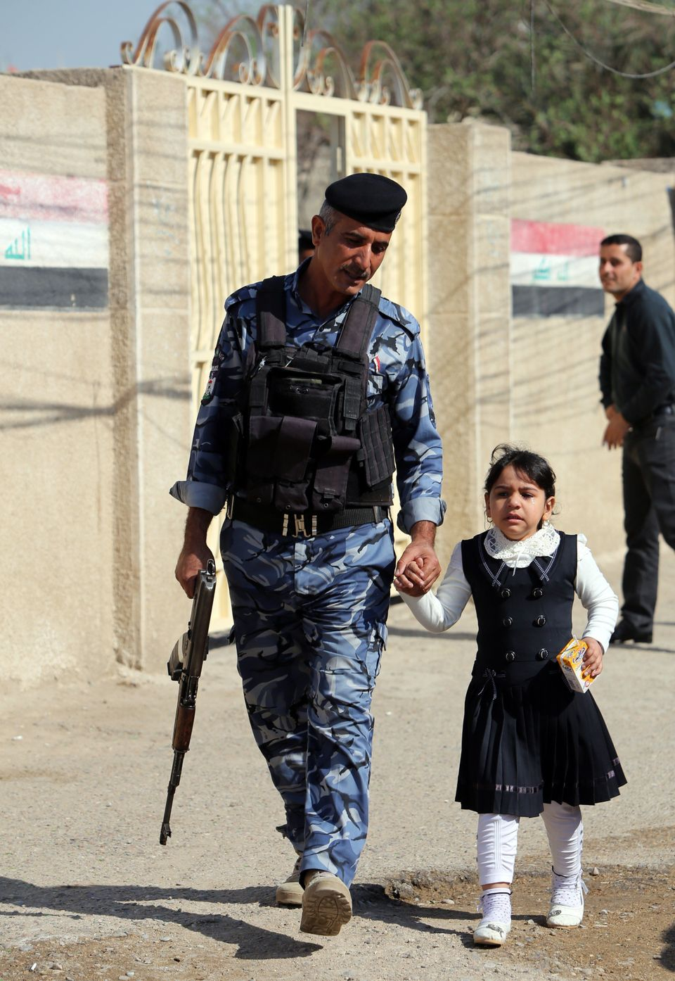 An Iraqi policeman holds a young girl's hand near the entrance to a school on the first day of...
