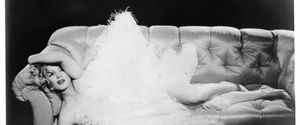 MARILYN MONROE LYING ON HER SIDE ON AN OVER STUFFED SOFA WITH LARGE FEATHERS COVERING HER IN A SCENE FROM THE FILM THE PRINCE AND THE SHOWGIRL 1957