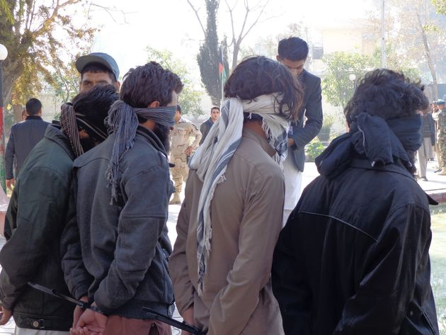 Four suspected members of the Islamic State are blindfolded by Afghan forces in Nangarhar,...