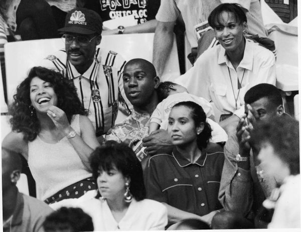 "Earvin ""Magic"" Johnson, center, wife Cookie and baby Earvin Johnson III, at a basketball game in August 1992. Cookie Johnson"