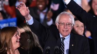 US Democratic presidential candidate Bernie Sanders waves during the primary night rally in Concord, New Hampshire, on February 9, 2016. Self-described democratic socialist Bernie Sanders and political novice Donald Trump won New Hampshire's presidential primaries Tuesday, US media projected, turning the American political establishment on its head early in the long nominations battle. / AFP / Jewel Samad        (Photo credit should read JEWEL SAMAD/AFP/Getty Images)