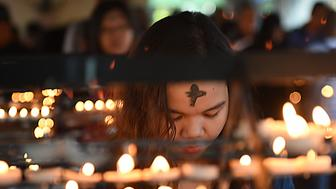 A woman next to lighted candles prays during the observance of Ash Wednesday at a church ground in Manila on February 10, 2016. The 40-day period of Lent begins on Ash Wednesday, with Catholics around the world observing the season which culminates in Easter Sunday.   AFP PHOTO / TED ALJIBE / AFP / TED ALJIBE        (Photo credit should read TED ALJIBE/AFP/Getty Images)