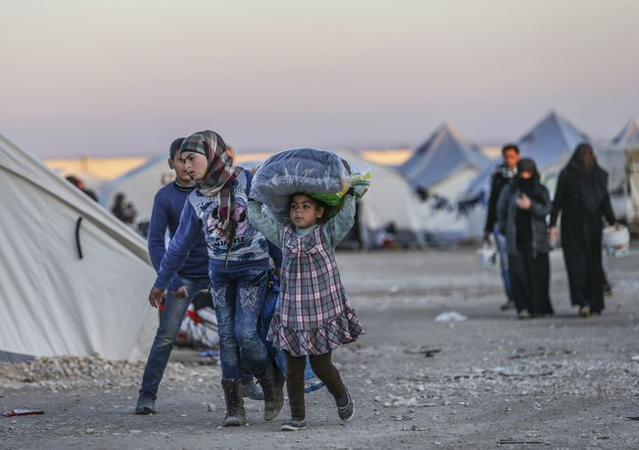 People take shelter near the Bab al Salameh border crossing on the Turkish-Syrian border north of Aleppo, Syria. Th