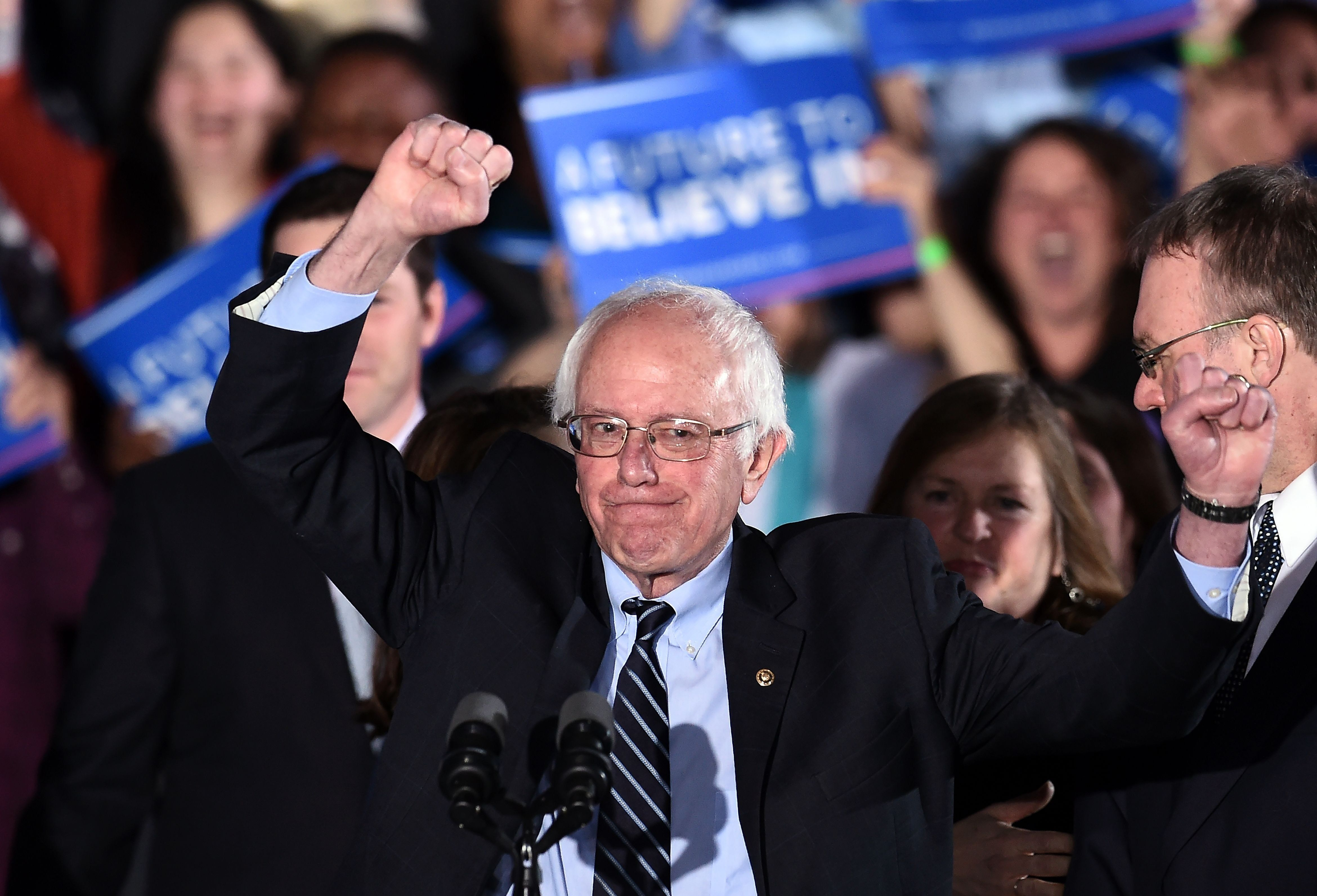 US Democratic presidential candidate Bernie Sanders celebrates victory during a primary night rally in Concord, New Hampshire, on February 9, 2016. Political novice Donald Trump and self-described democratic socialist Bernie Sanders won New Hampshire's presidential primaries Tuesday, US media projected, turning the American political establishment on its head early in the long nominations battle. / AFP / Jewel Samad        (Photo credit should read JEWEL SAMAD/AFP/Getty Images)