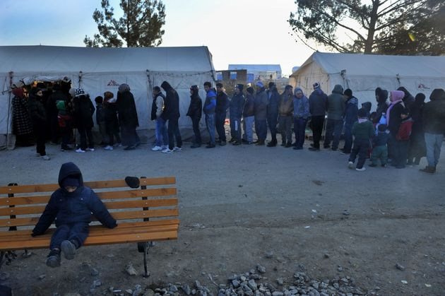 Migrants and refugees line up to receive clothes near Idomeni, Greece, by the Macedonian