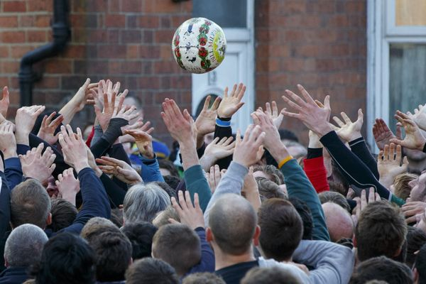 Rival teams 'Up'ards' and 'Down'ards' battle for the ball during the second day of the Royal Shrovetide Football match in Ash