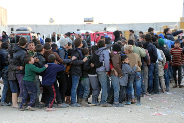 Syrians, who fled bombing in Aleppo, wait in line to get food at a tent city on the Turkish-Syrian