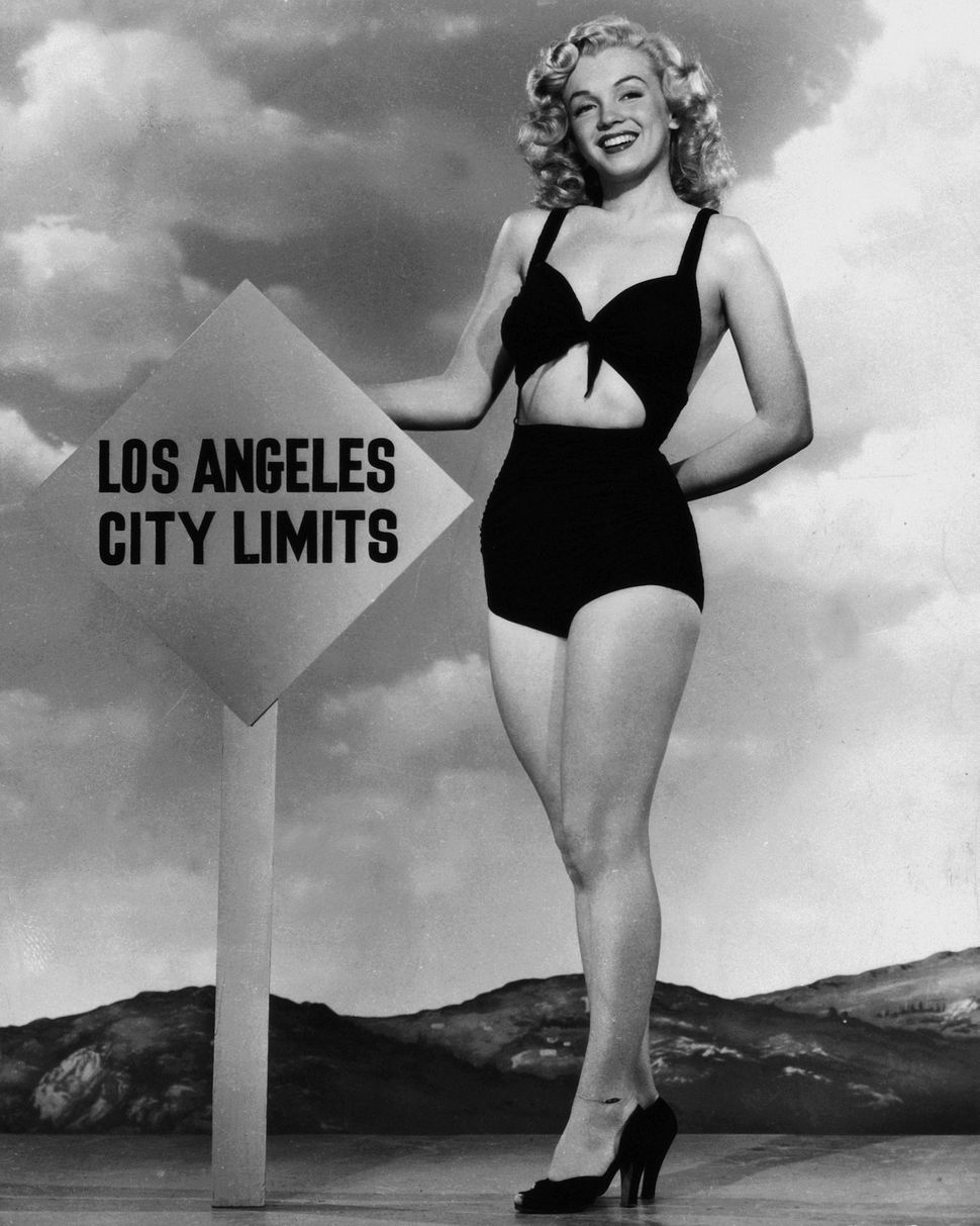 Marilyn Monroe smiling next to a Los Angeles road sign.