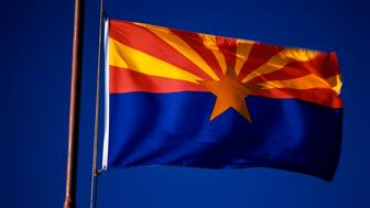 This is the Arizona State Flag waving in the wind. It is situated on a flagpole against a blue sky. At the center of the flag is a star.