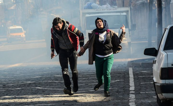 """Residents of Diyarbakir in Turkey's Kurd-dominated southeast run for cover from tear gas fired by security forces on Jan. 27. Amnesty International calls Turkey's treatment of civilians in the region """"collective punishment."""""""