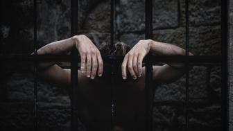 A man hanging depressed on the bars of a prison cell. Evokes emotion and conceptual feelings about prison.
