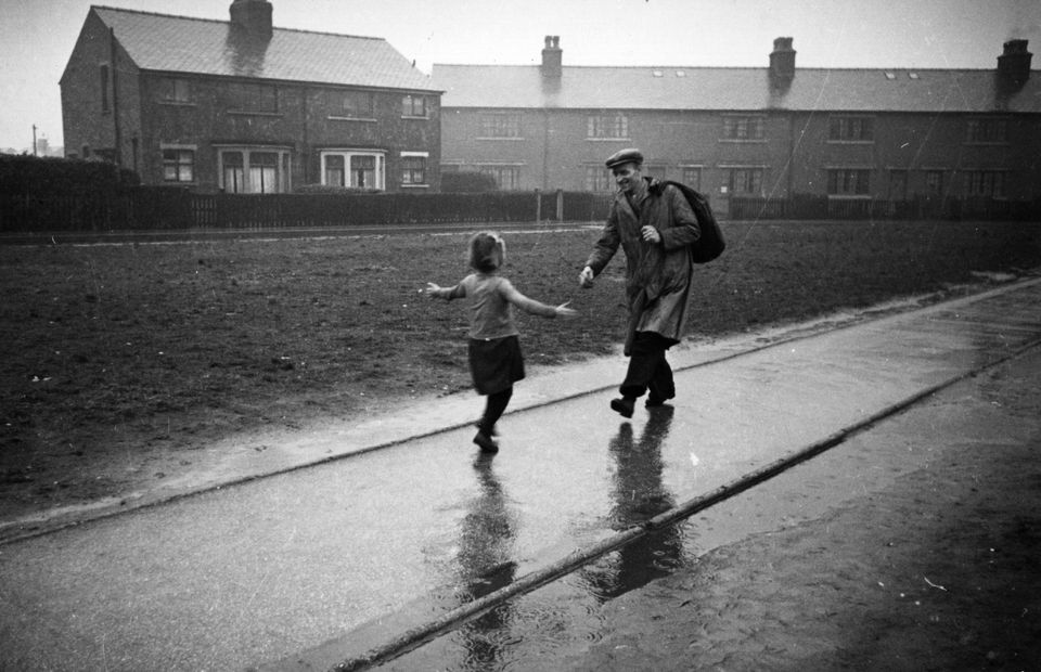 A little girl runs to meet her father on his return from work in March