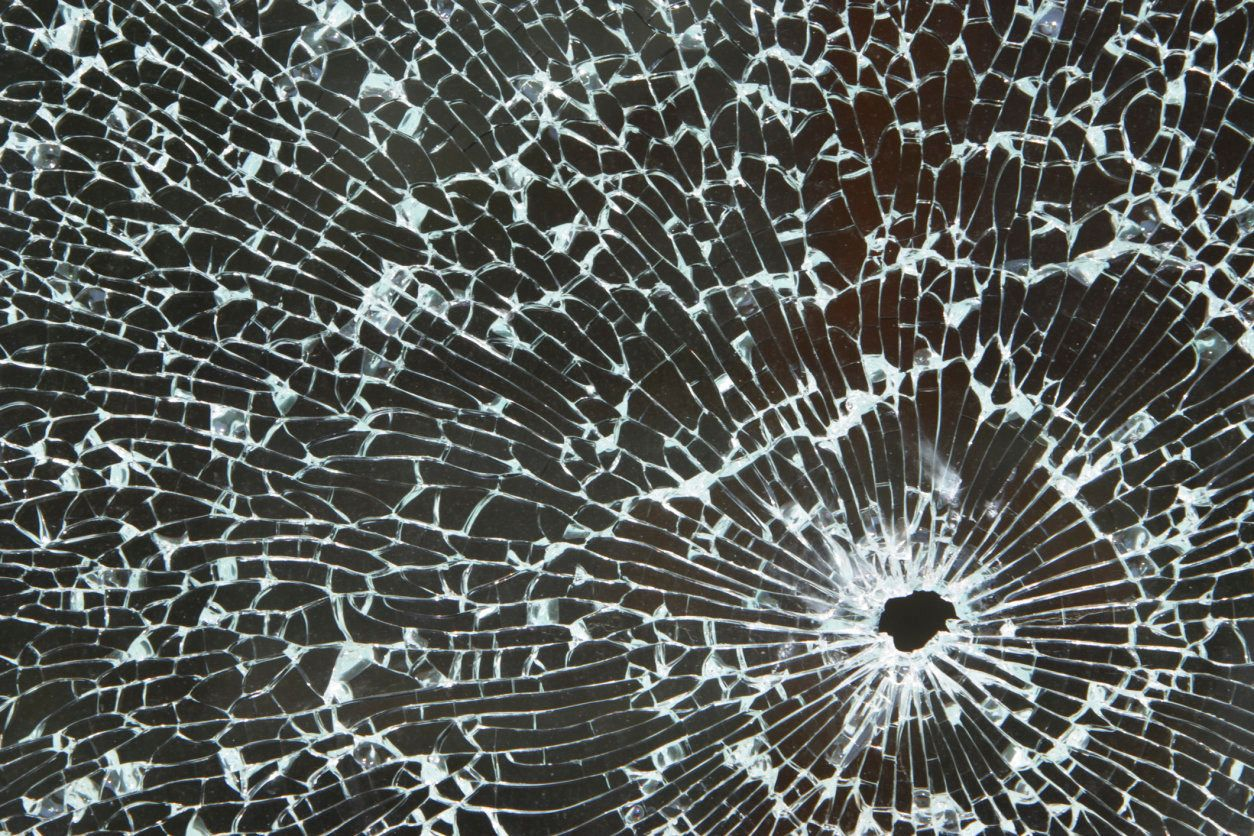 Broken glass with bullet hole