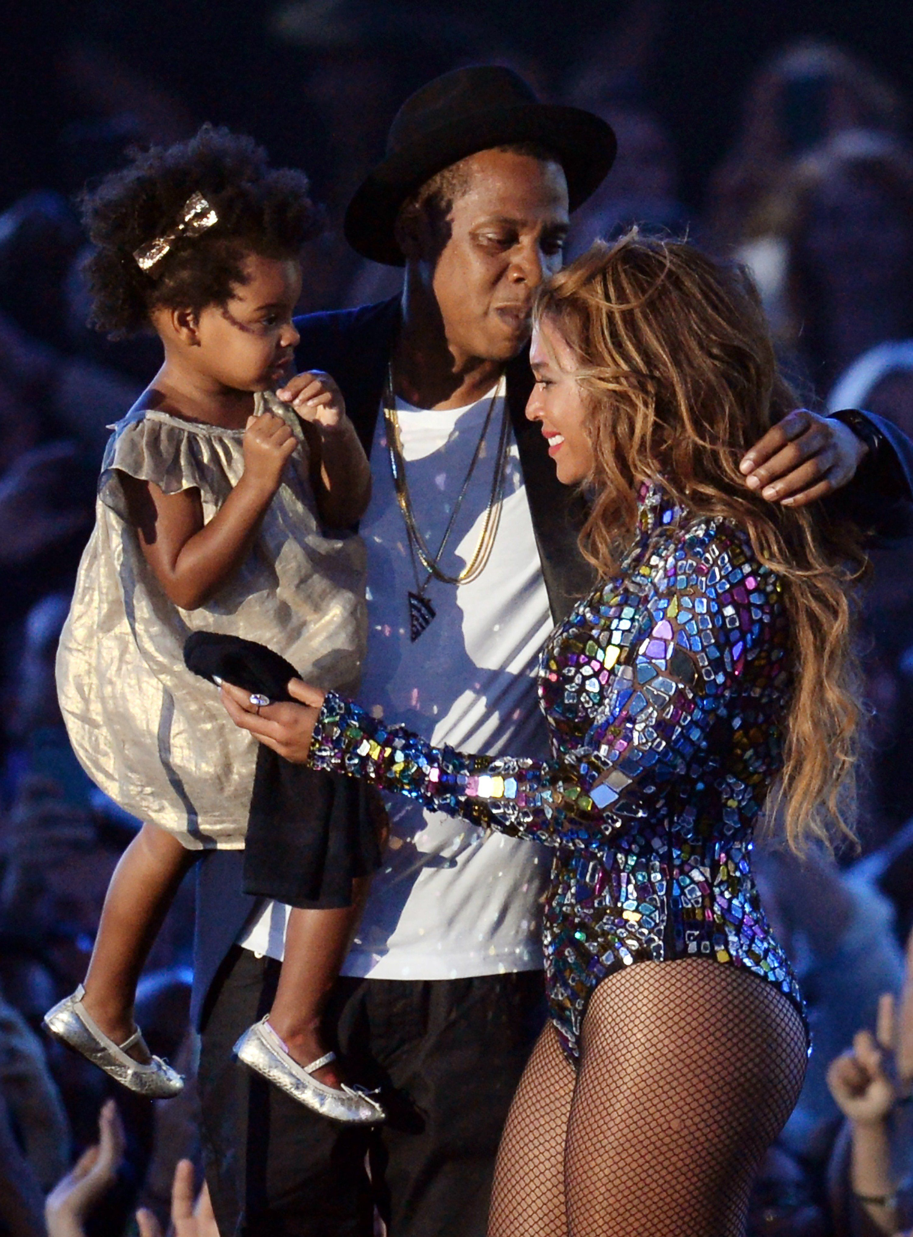 Recording artist Jay-Z (C), holding their daughter Blue Ivy Carter (L), kisses Beyonce on stage at the MTV Video Music Awards (VMA), August 24, 2014 at The Forum in Inglewood, California. AFP PHOTO / Robyn Beck        (Photo credit should read ROBYN BECK/AFP/Getty Images)