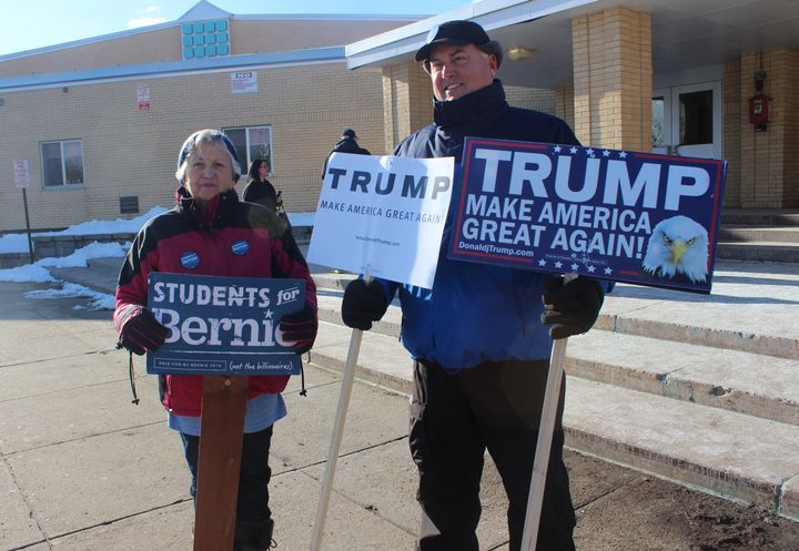 Jim Bennett and Sandy Paradis stand in front of a polling location in Manchester, New Hampshire, on Tuesday.