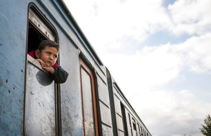 A boy looks out the train window on the migrant trail to Europe, where thousands have fled violence in countries such as Syri