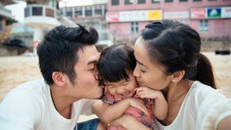 Mom & dad hugging and kissing lovely toddler girl on her cheeks while toddler girl smiling joyfully.