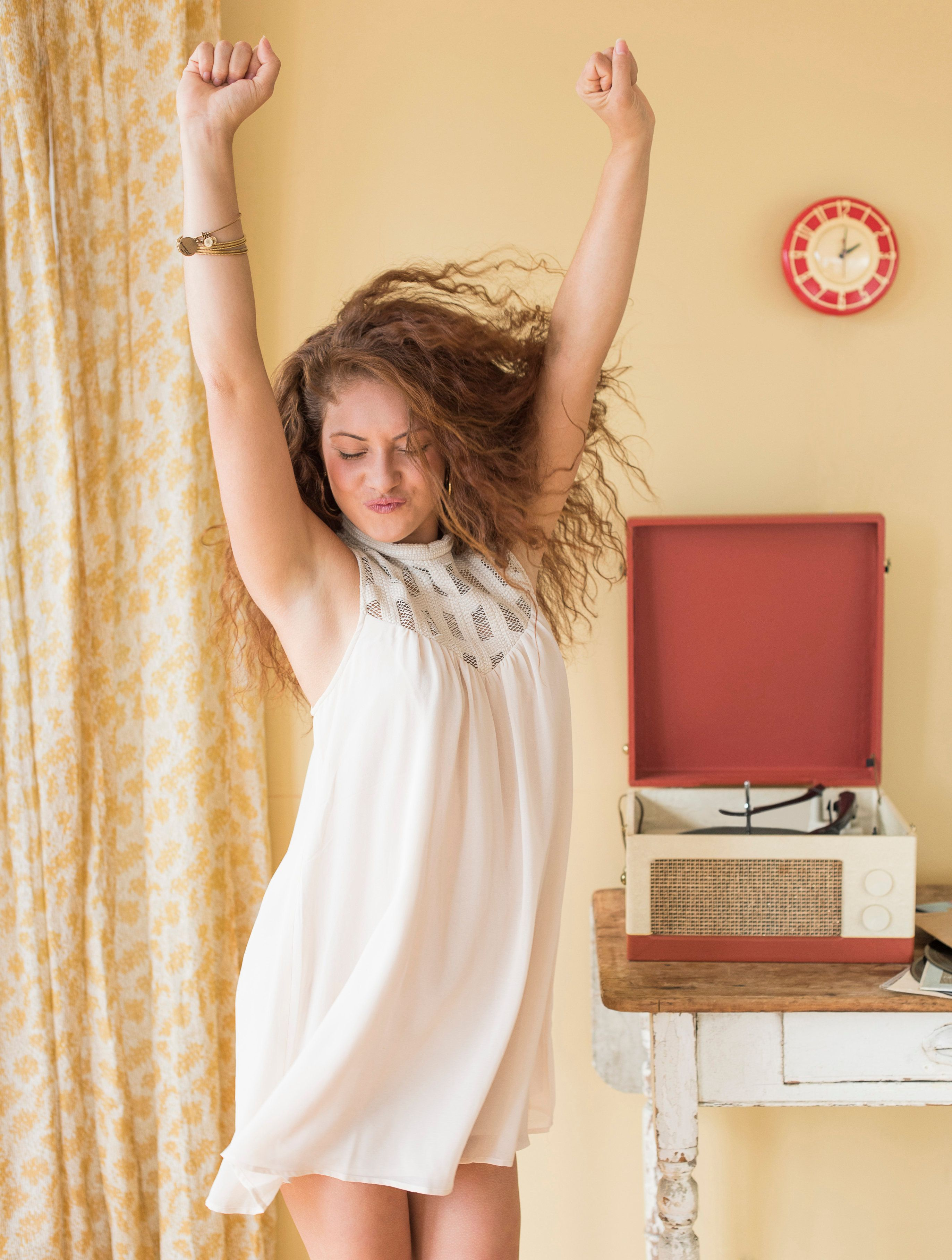 USA, New Jersey, Jersey City, Portrait of woman dancing happily in room