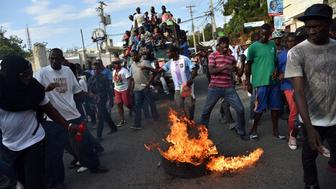 TOPSHOT - Demonstrators of opposition political parties march during a protest against Haitian President Michel Martelly, in Port-au-Prince, on February 6, 2016. Haitian politicians inked a last-minute agreement to install a transitional government, just hours before President Michel Martelly was scheduled to step down with no replacement in line.  / AFP / HECTOR RETAMAL        (Photo credit should read HECTOR RETAMAL/AFP/Getty Images)
