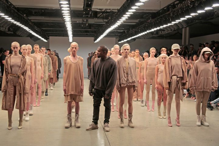 Kanye West poses alongside models wearing khaki hues during the finale of Yeezy Season 2 during New York Fashion Week at Skylight Modern on September 16, 2015 in New York City.