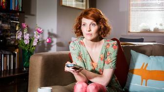 Woman watching tv in livingroom.