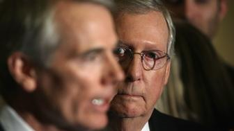 WASHINGTON, DC - JANUARY 20:  U.S. Senate Majority Leader Sen. Mitch McConnell (R-KY) (R) listens as Sen. Rob Portman (R-OH) (L) speaks during a media briefing after the Senate Republican weekly policy luncheon at the U.S. Capitol January 20, 2015 on Capitol Hill in Washington, DC. Senate Republicans held the luncheon to discuss GOP agenda.  (Photo by Alex Wong/Getty Images)