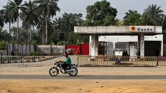 A man rides a motorcycle past a closed Oando Plc gas station in Port Harcourt, Nigeria, on Thursday, Jan. 14, 2016. With his security forces engaged in fighting Boko Haram's Islamist insurgency in the north, President Muhammadu Buhari can't afford renewed rebellion in the delta. Photographer: George Osodi/Bloomberg via Getty Images