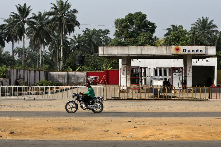 A man rides a motorcycle past a closed gas station in Port Harcourt, Nigeria, on Jan. 14, 2016. Plummeting global oil prices
