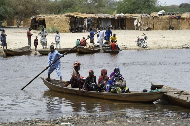 People cross a branch of Lake Chad in April 2015. The lake has shrunk by 90 percent since the 1960s.