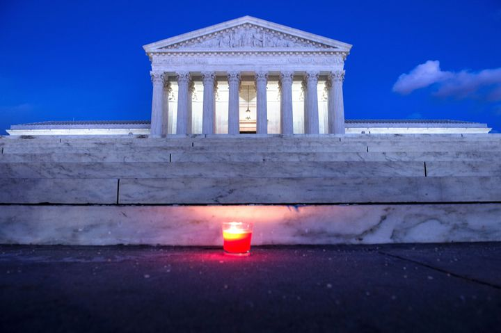 A candle is seen at the steps of the U.S. Supreme Court on Saturday following the announcement of the death of Justice A